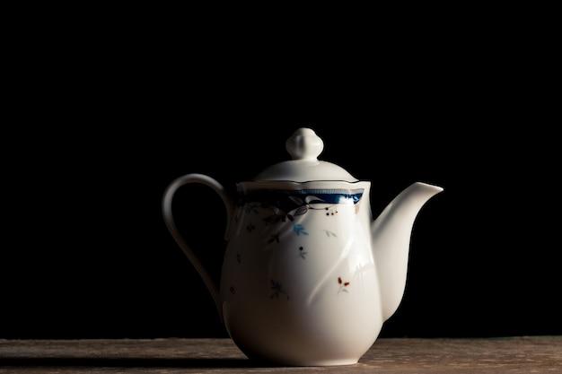 Керамический чайный горшок на столе, черный фон.