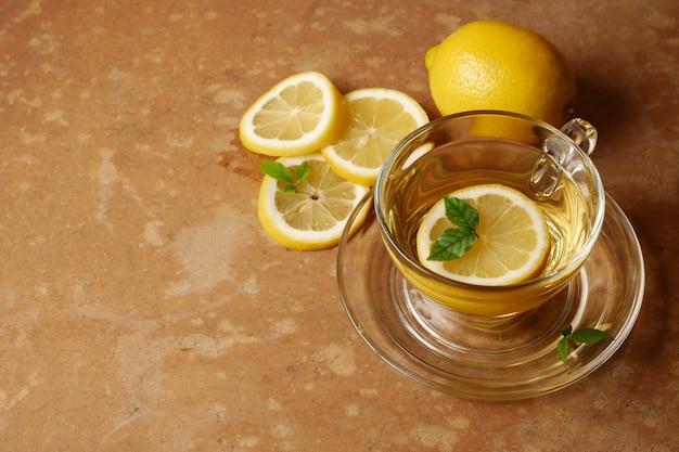 Чашка чая и лимона на фоне коричневый гранж.