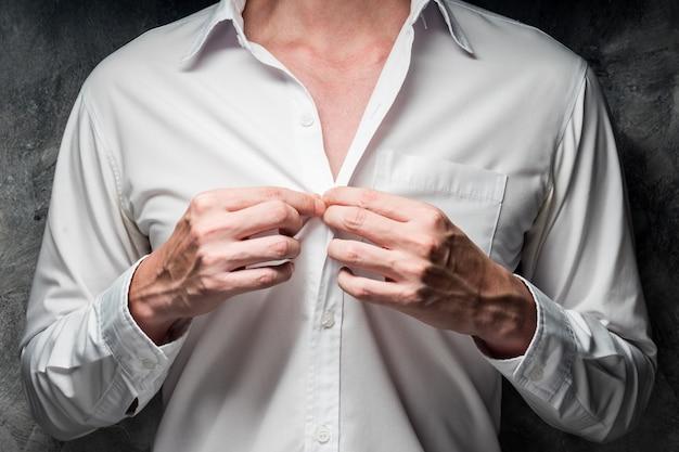 Закройте человека, сняв белую рубашку на сером фоне гранж