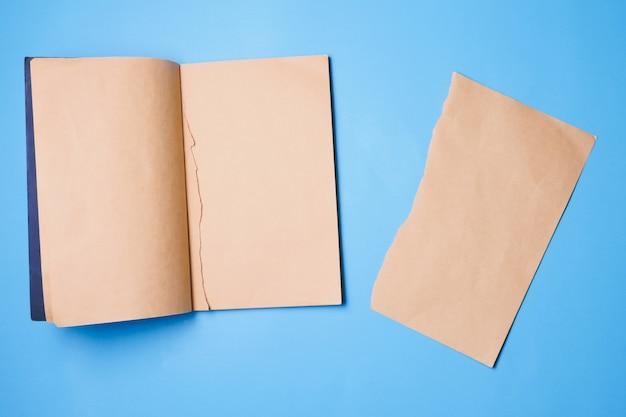 Пустой ноутбук с куском бумаги для заметок на синем фоне.