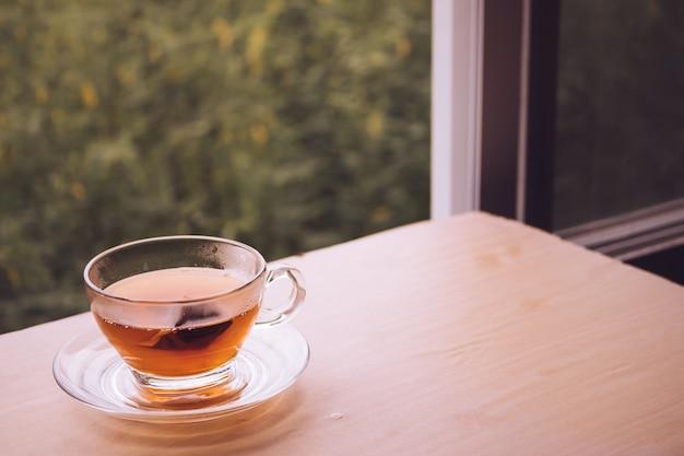 Чашка чая на деревянный стол, чайный пакетик в стекле, природа фон. свободное место для текста