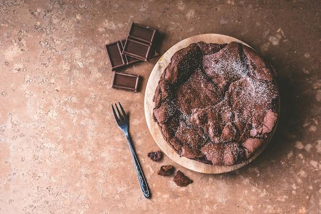 フォーク付きの木製トレイにチョコレートケーキのトップビュー。
