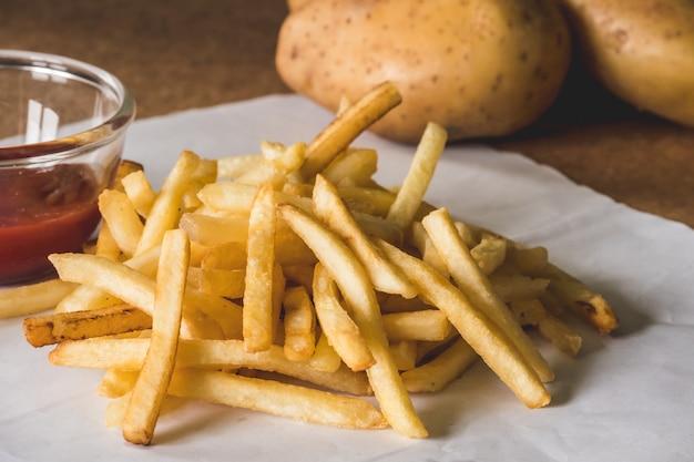 Закройте картофель фри с кетчупом и сырым картофелем на деревянном столе.