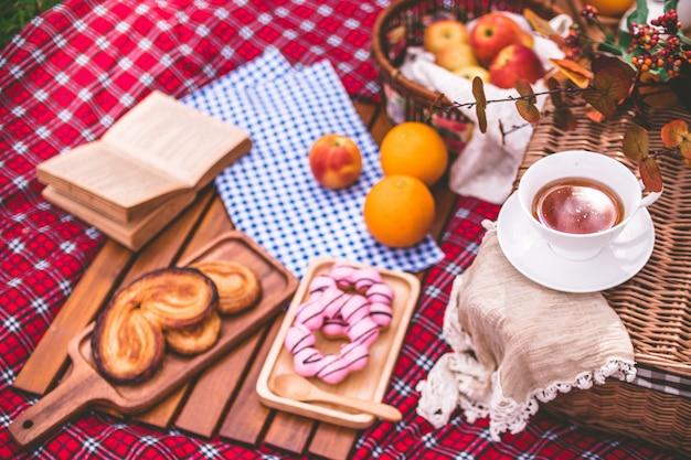 公園の毛布に食物のバスケットを持つ夏のピクニック。