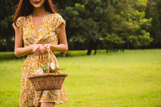 Крупным планом женщина в желтом платье, держа корзину с цветами, стоя на зеленой траве