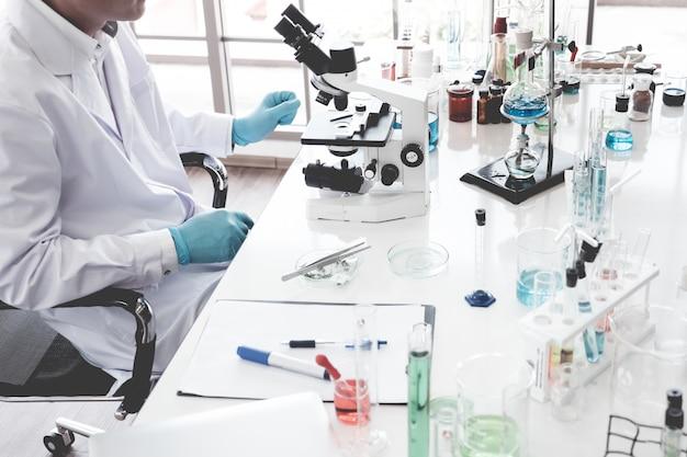 科学者が研究を行い、実験室で顕微鏡を通して見る