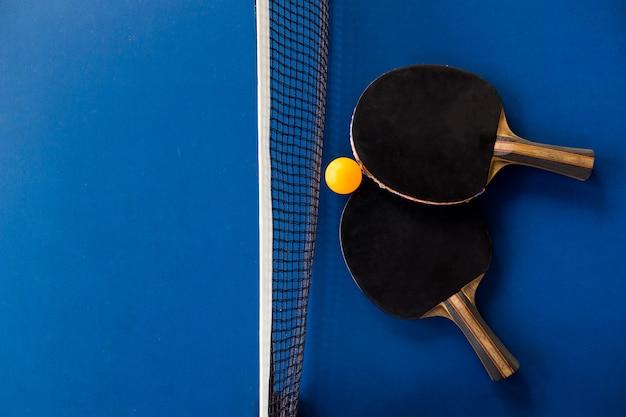 卓球ラケットと青の背景にボール。