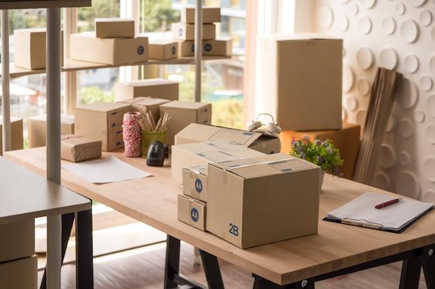 オフィスで木製のテーブルの上の商品の多くの箱。