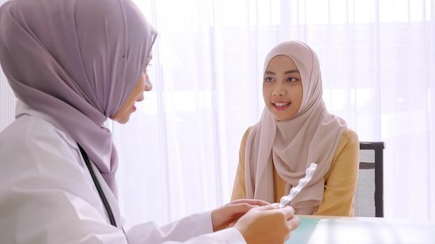 病室で患者に錠剤を与えるイスラム教徒の女性医師。