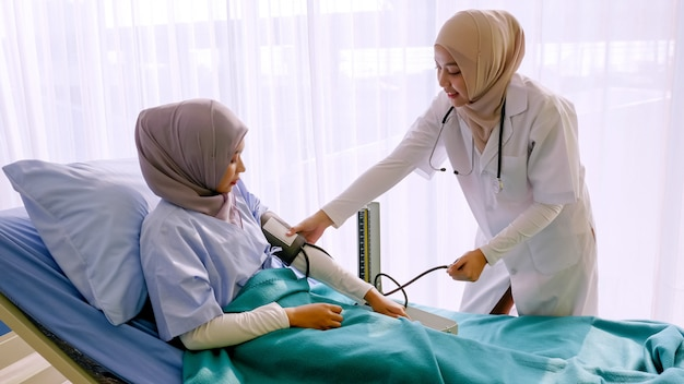 イスラム教徒の女性医師が病室で患者の血圧をチェックします。
