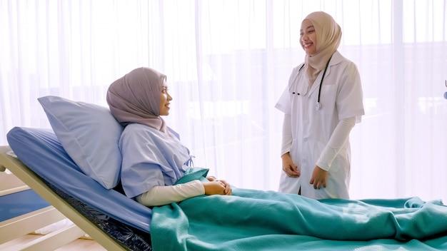 イスラム教徒の女性医師が病室で患者と話しています。
