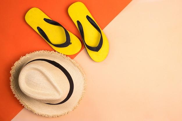 Шляпа пляжа и резиновые тапочки на предпосылке цветов.