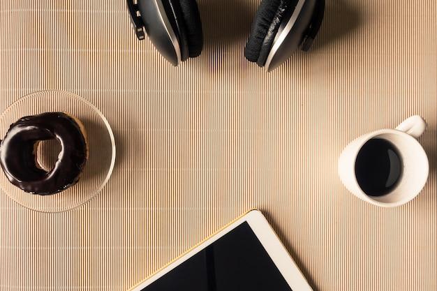 Вид сверху наушников с планшетом, чашкой кофе и пончиком на столе. свободное место для текста