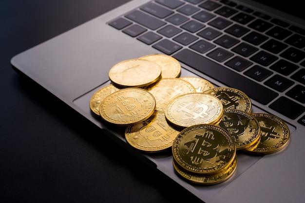 コンピューター上のビットコインシンボルと黄金のコイン。