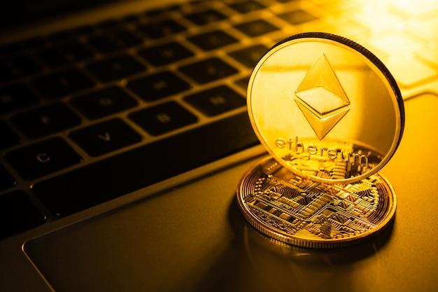 コンピューター上のイーサリアムシンボルと黄金のコイン。