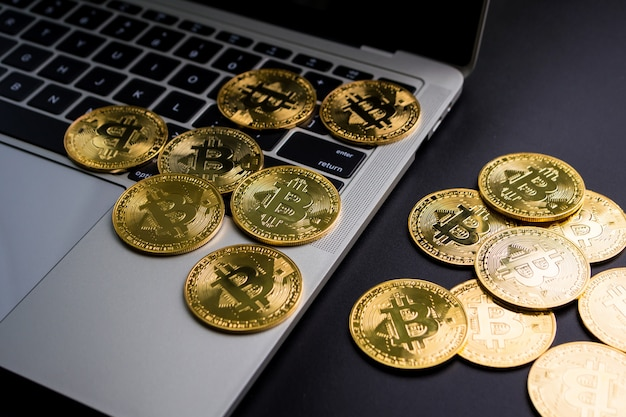 コンピューターのキーボードのビットコインシンボルと黒の背景の黄金のコイン。