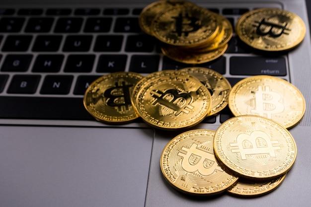 コンピューターのキーボード上のビットコインシンボルと黄金のコイン。