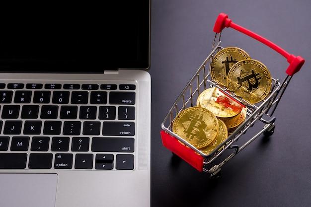 小さなショッピングカートとコンピューターでビットコインシンボルと黄金のコイン。