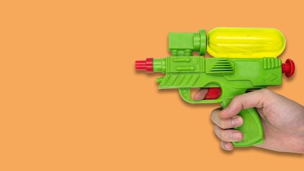 オレンジの背景に銃の水のおもちゃを保持して手。テキストの空き領域