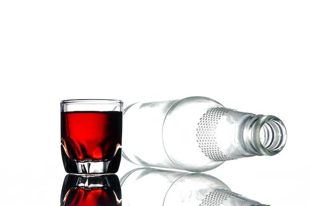 アルコールと空のボトルのガラスは、白い背景に。