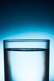 青い背景に水のガラス。