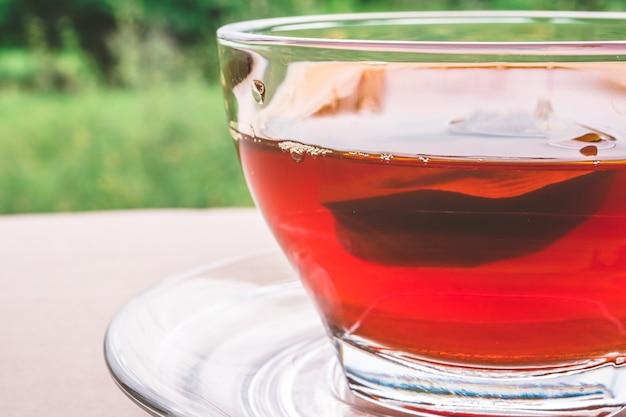Чашка чая на деревянный стол, чайный пакетик в стекле, природа фон.