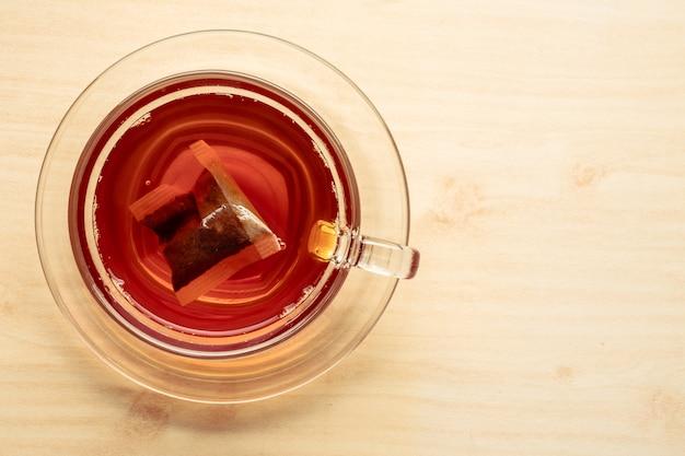 Чашка чая на деревянном столе, чайный пакетик в стакане.