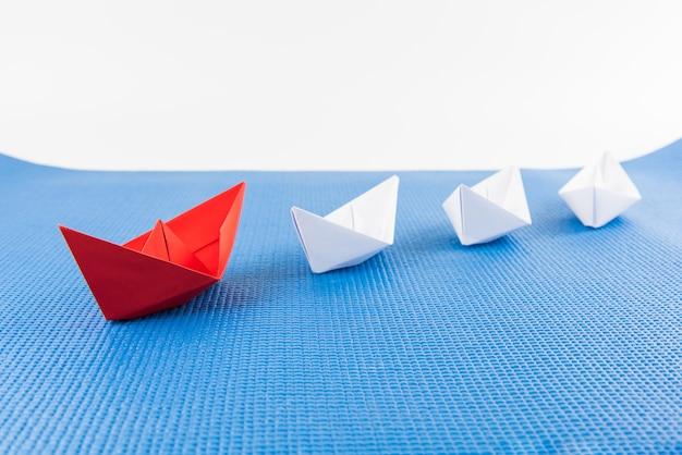 Концепция лидерства с красным бумажным кораблем, ведущим среди белого и синего фона