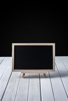 木製の床と黒い背景のスタンドの黒板