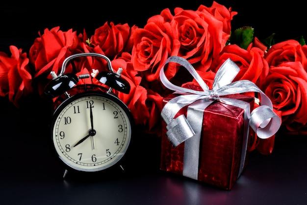 目覚まし時計、ギフトボックス、バッグ、黒の背景に赤いバラ