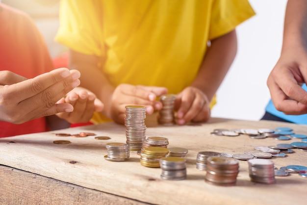 子供たちの手がコインを貯金箱に入れるのを助けている