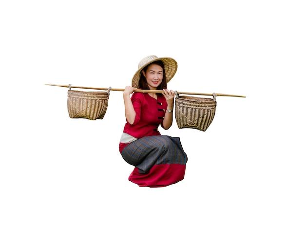 タイのドレスを着た美しい女性が肩にバスケットを運ぶ