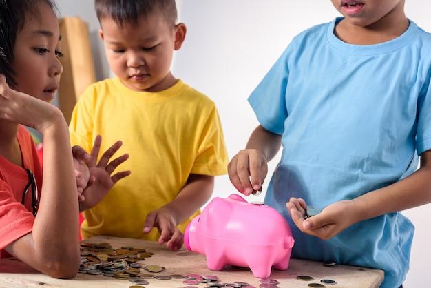 アジアの子供たちのグループは白い背景の上の貯金箱にコインを入れるのを助けています。