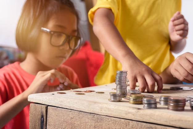 アジアの子供たちのグループは、貯金箱にコインを入れるのを助けています