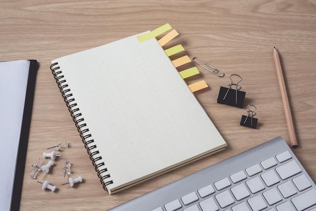 日記またはノートブックとクリップボード、キーボード、鉛筆、付箋のあるワークスペース