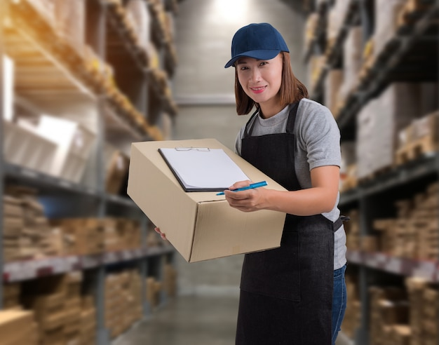 女性スタッフ商品の配達小包箱で商品受領書にサインをする