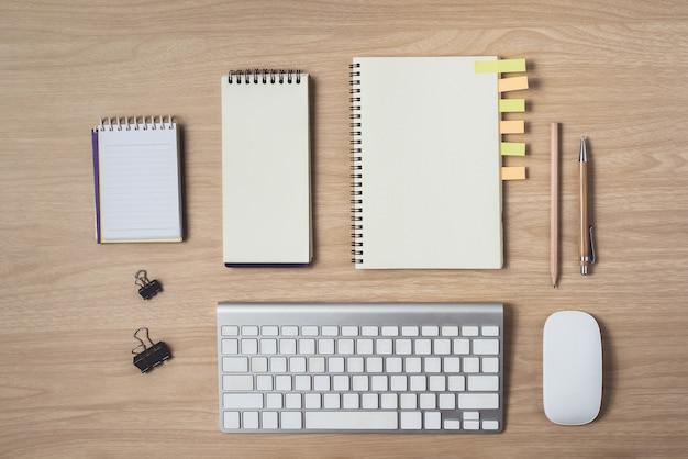 日記またはノートブックとクリップボード、マウス、キーボード、鉛筆、付箋を含むワークスペース