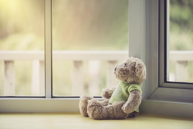 Одинокая кукла медведей возле окна