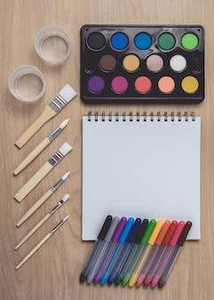 茶色の木のテーブルに多くのカラフルなペン、絵筆、水彩パレットを備えたメモ帳またはノートブック。
