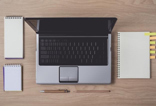 ノートブックと木製の背景上のラップトップのワークスペース