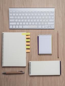 ノートブックと木製の背景にキーボードとワークスペース
