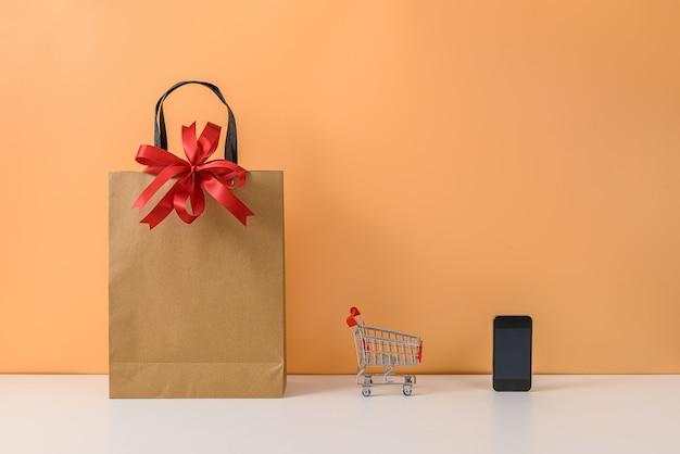 Бумажные сумки и тележка или тележка на белом столе и пастельно-оранжевая стена