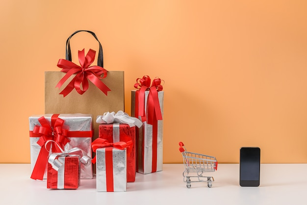 紙の買い物袋とショッピングカートまたはトロリー、多くのギフトボックス、白いテーブルとパステルオレンジの壁にスマートフォン