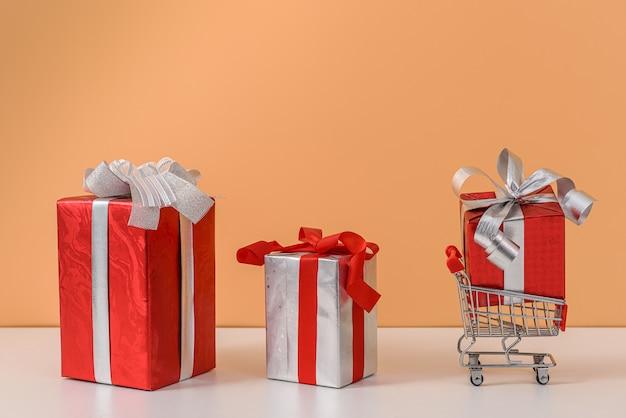 赤いリボンの弓とショッピングカートまたは白いテーブルとパステルオレンジの壁にトロリーの多くのギフトボックス