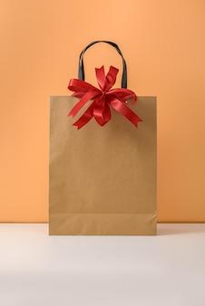 赤いリボンの弓とハンドルが付いたクラフトパッケージまたは茶色の紙のショッピングバッグ。