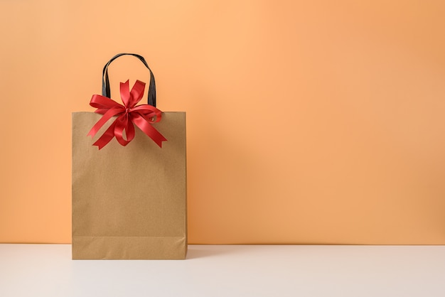 空白のクラフトパッケージまたは赤いリボン弓とハンドル付きの茶色の紙の買い物袋のモックアップ