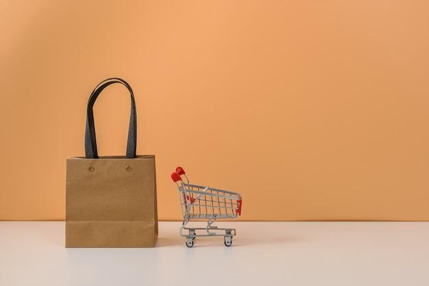 紙の買い物袋とショッピングカートまたは白いテーブルとパステルオレンジの壁にトロリー