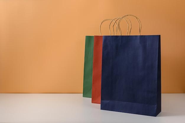 空白のクラフトパッケージまたはハンドル付きのカラフルな紙の買い物袋のモックアップ