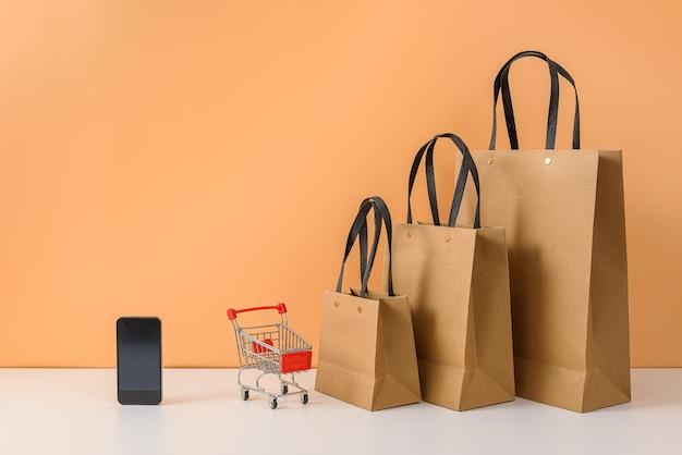 紙の買い物袋とショッピングカートまたは白いテーブルとパステルオレンジの壁にスマートフォンでトロリー