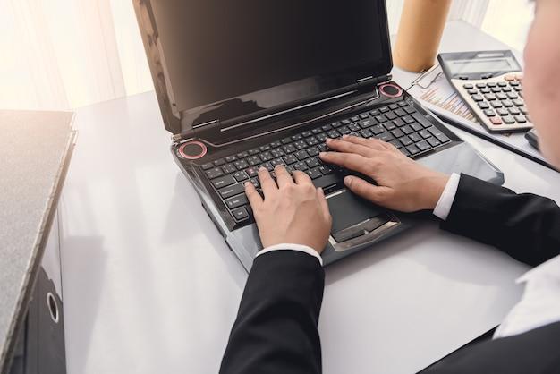 Закрыть под рукой деловая женщина, используя портативный компьютер в офисе